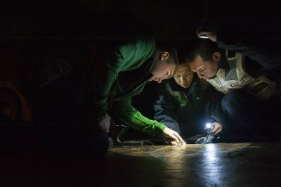 Three people inspecting floor
